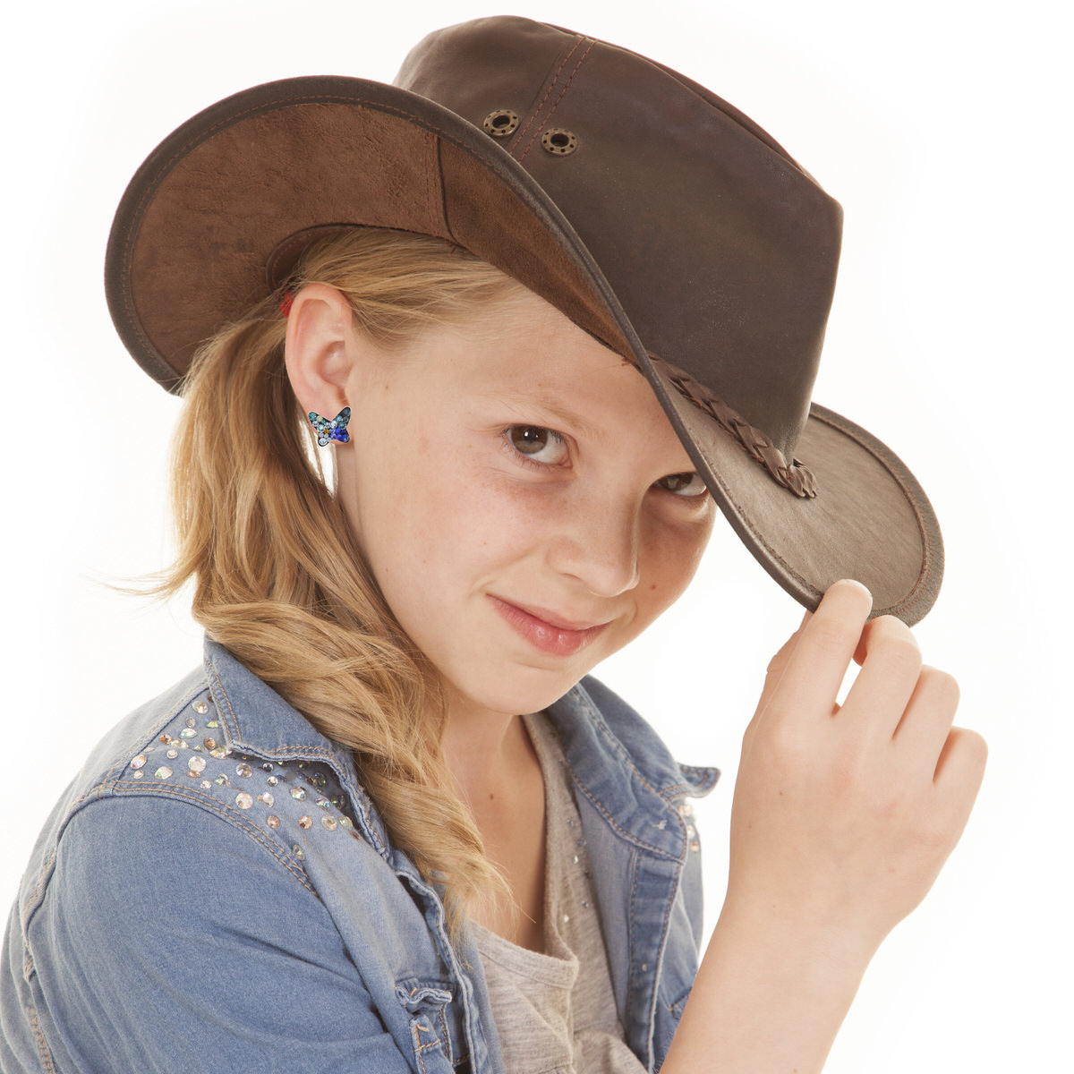 a young girl holding on to the rim of her hat with a small smile on her face..