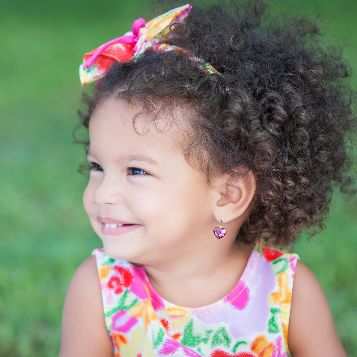 Side portrait of a small hispanic girl with an afro hairstyle smiling with diffused green grass background